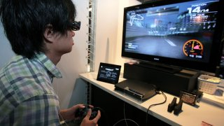 A visitor plays 'Ridge Racer 7' on a 3D-supported PlayStation 3