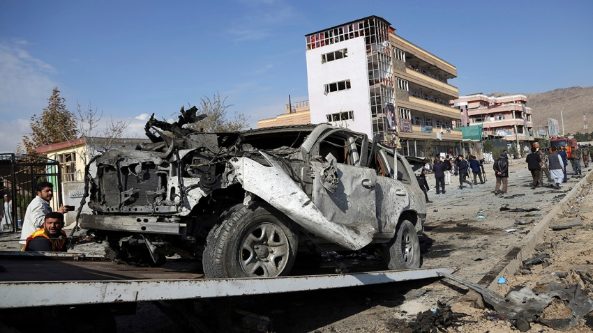 In this Nov. 13, 2019, file photo, Afghan security personnel remove a damaged vehicle after a car bomb attack in Kabul, Afghanistan.