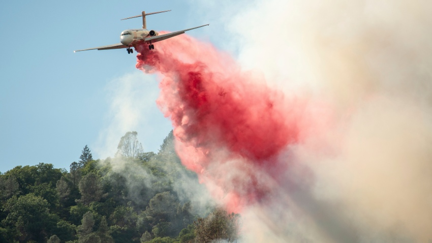 In this Sunday, Aug. 5, 2018, file photo, an air tanker drops fire retardant on a burning hillside in the Ranch Fire in Clearlake Oaks, Calif.