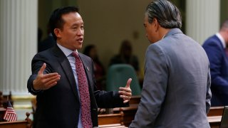 Assemblyman David Chiu, D-San Francisco, left, speaks with Assemblyman Rob Bonta, D-Alameda, during the Assembly session in Sacramento, California, Jan. 9, 2020. Chiu has introduced a bill to eliminate the mortgage interest deduction on vacation homes and use the money to pay for homeless services. The bill would also lower the amount of mortgage interest people could claim for their primary homes on their state taxes.