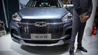A staff member stands next to a Tiggo 8 SUV by Chinese automaker Chery after a press conference at the China Auto Show in Beijing. April 25, 2018. A California company says it will build and sell Chinese-designed automobiles in the U.S. at the end of next year or early in 2022.