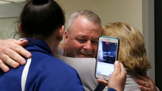 Maureen Klein, right, hugs her son Ricky Davis, center, after he was released from custody at the El Dorado County Jail in Placerville, California, Thursday, Feb. 13, 2020. Davis spent about 15 years in prison after being wrongly convicted of second-degree murder in the stabbing death of his housemate, a newspaper columnist, in 2004. The conviction was thrown out after new evidence was found implicating another person.