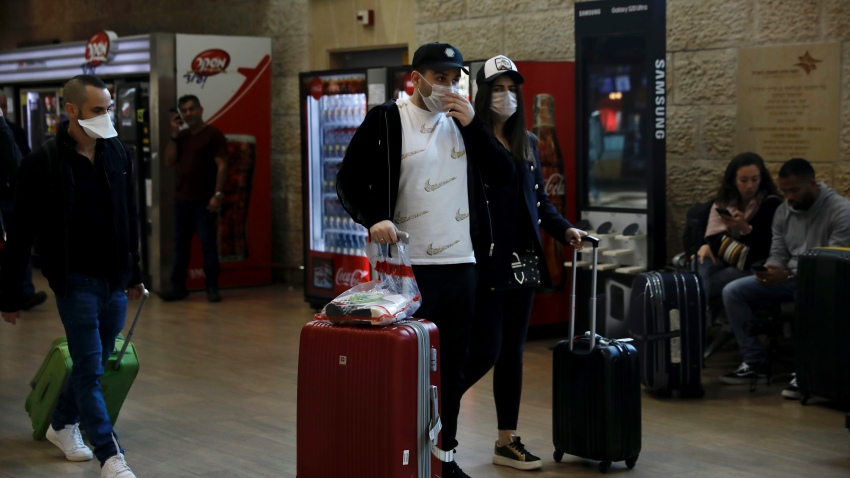 Passengers wearing protective masks arrive in Ben Gurion Airport near Tel Aviv, Israel, Thursday, Feb. 27, 2020. Israel on Wednesday advised its citizens to reconsider all foreign travel amid the global spread of the new coronavirus that was first reported in China. (AP Photo/Ariel Schalit)