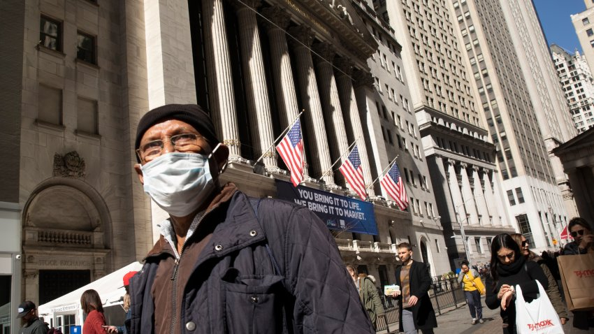 In this March 6, 2020, file photo, a man wears a mask as he passes the New York Stock Exchange in New York City.