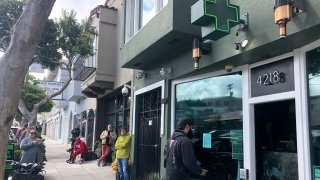 """Customers maintain social distance while waiting to enter The Green Cross cannabis dispensary in San Francisco, March 18, 2020. As about 7 million people in the San Francisco Bay Area are under shelter-in-place orders, only allowed to leave their homes for crucial needs in an attempt to slow virus spread, marijuana stores remain open and are being considered """"essential services."""""""