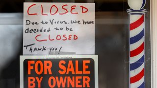 """In this April 2, 2020, file photo, """"For Sale By Owner"""" and """"Closed Due to Virus"""" signs are displayed in the window of Images On Mack in Grosse Pointe Woods, Mich."""