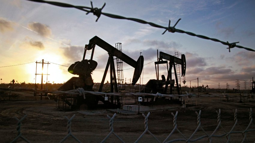the sun sets beyond pumpjacks operating at the Inglewood oil fields in the Baldwin Hills area of Los Angeles