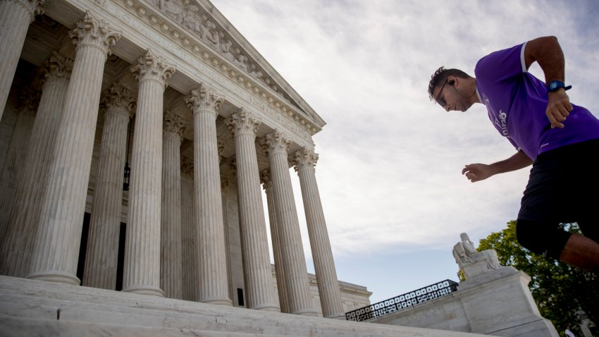 A man exercises on the steps of the Supreme Court where the justices will hold arguments by telephone for the first time ever, Monday, May 4, 2020, in Washington.