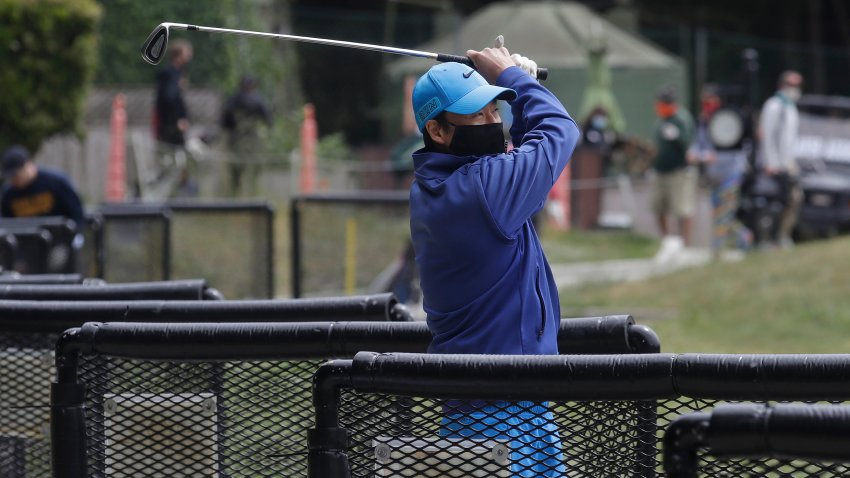 Cam Kim wears a face mask while hitting from the driving range at Presidio Golf Course during the coronavirus outbreak in San Francisco, Sunday, May 10, 2020.