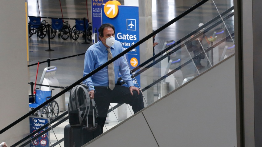 In this May 11, 2020, file photo, a traveler wears a face mask as he goes to the boarding gates at Sacramento International Airport in Sacramento, Calif.