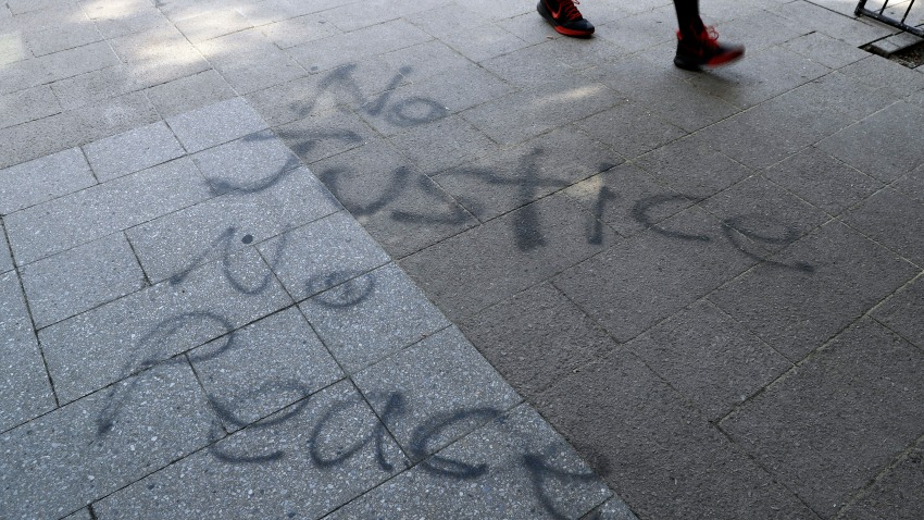 "A man walks past ""No Justice No Peace"" spray painted on a sidewalk in downtown Louisville, Ky., June 2, 2020."