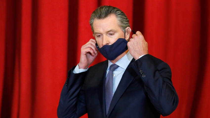 California Gov. Gavin Newsom takes off his face mask before a news conference, June 1, 2020, in Sacramento, California. A Chinese company paid by California to manufacturer hundreds of millions of protective masks missed a Sunday deadline for federal certification, marking the second times its shipments to the state will be delayed.