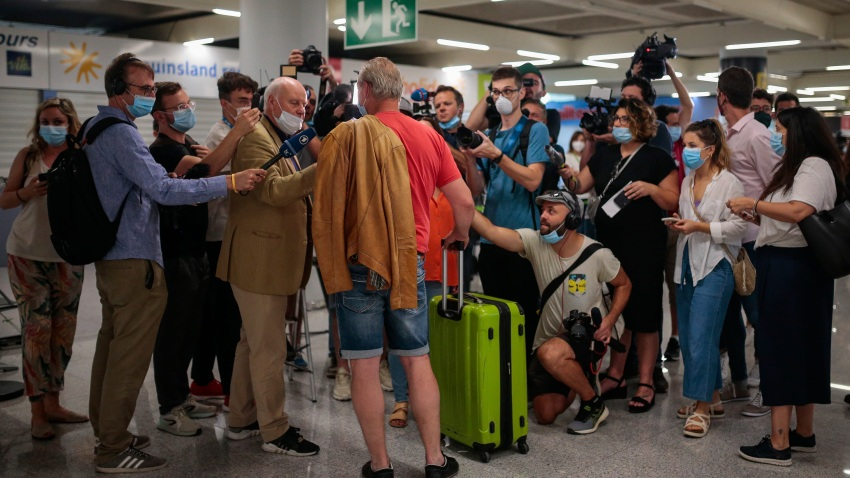 A TUI X3 2312 Duesseldorf-Mallorca flight passenger talks to the press at Son Sant Joan airport in Palma de Mallorca, Spain, Monday, June 15, 2020. Borders opened up across Europe on Monday after three months of coronavirus closures that began chaotically in March. But many restrictions persist, it's unclear how keen Europeans will be to travel this summer and the continent is still closed to Americans, Asians and other international tourists.