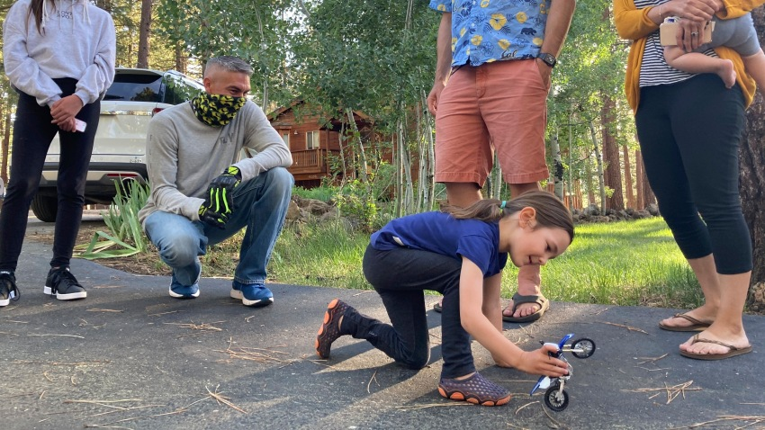 Vivian Filipic, 4, plays with a toy motorcycle in a driveway in Truckee, Calif., Friday, June 19, 2020, the day before her fifth birthday, in front of, from left, Scarlett Fierro, Craig Fierro, Vivian's parents Filip Filipic and Kirsten Mickelson, and her brother Luca Filipic, 9 months. Craig Fierro, who owns a motorcycle shop in the city, has brought dozens of the toys to local kids during the coronavirus pandemic over the last two months to brighten their birthdays during shelter-at-home and social-distancing directives.