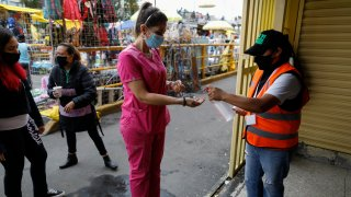 A shopper is given antibacterial gel as she enters a market