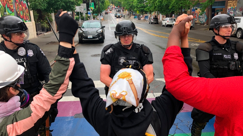 Protesters stand holding up their arms in front of a road blocked by police in the Capitol Hill Organized Protest zone early Wednesday, July 1, 2020, in Seattle. Police in Seattle have torn down demonstrators' tents in the city's so-called occupied protest zone after the mayor ordered it cleared.