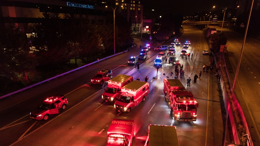 Emergency personnel work at the site where a driver sped through a protest-related closure on the Interstate 5 freeway in Seattle