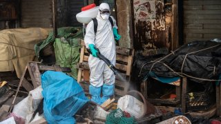 In this March 22, 2020, file photo, a municipal worker sanitizes the street of Dakar's popular Medina neighborhood after a bulldozer demolished informal shops in an effort to stop the spread of the coronavirus.
