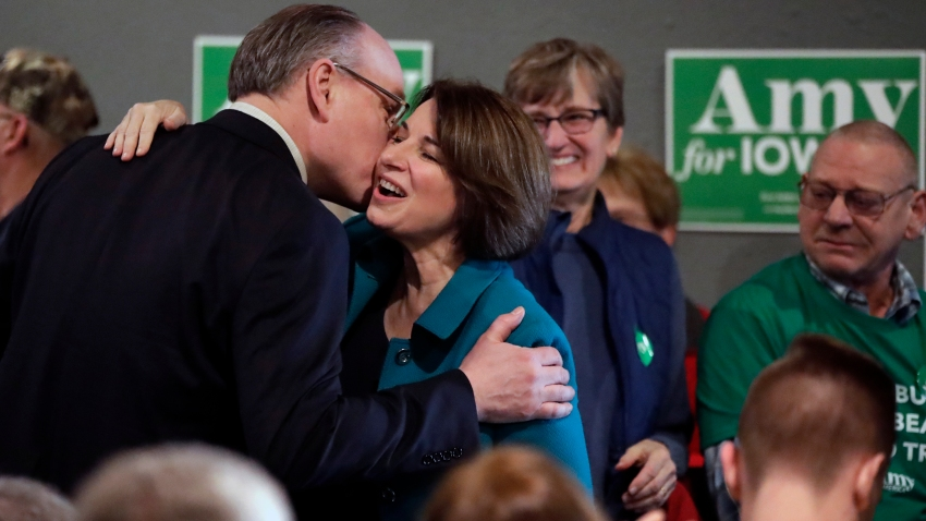 In this Feb. 1, 2020, file photo, Democratic presidential candidate Sen. Amy Klobuchar, D-Minn., center, gets a kiss from husband John Bessler upon arriving at a rally in Sioux City, Iowa.