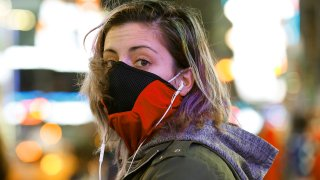 Brooklyn resident and waitress Casey Stewart peers out from a ski mask she adapted to protect herself from coronavirus after riding the subway to Times Square, March 12, 2020, in New York. She is also wearing a protective mask beneath the ski mask.