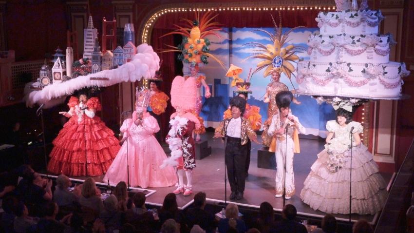 Performers line up at the front of the stage wearing colorful hats and costumes.