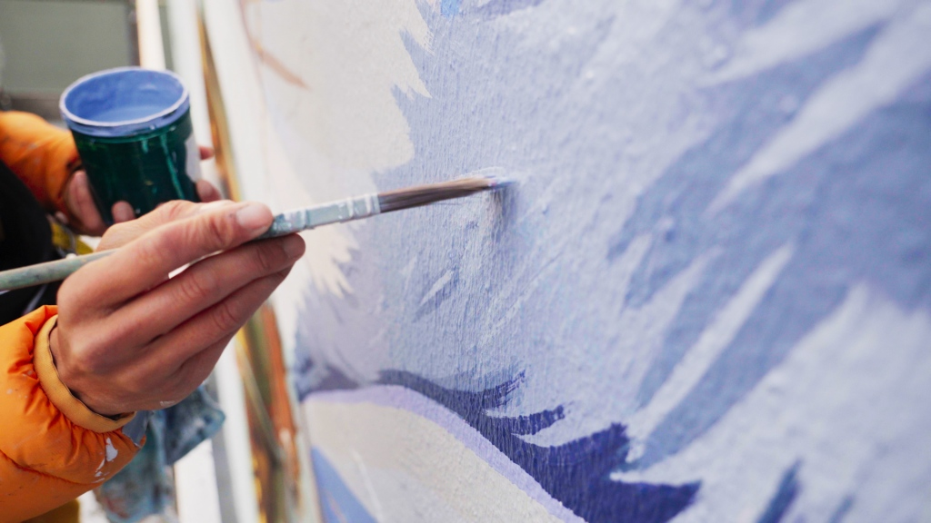 a painter with blue paint brushes it onto a wall