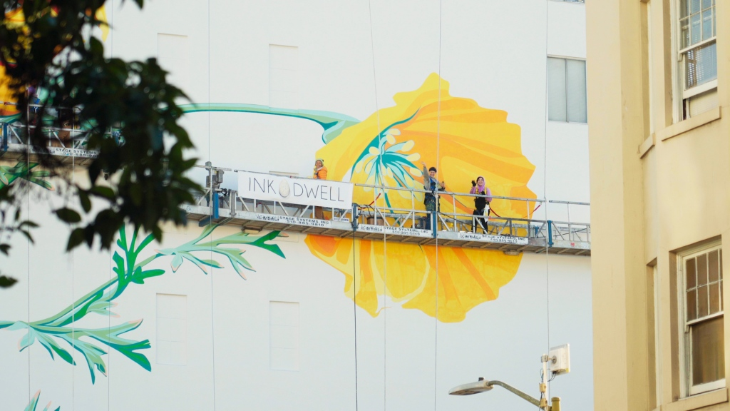 painters working on a giant butterfly mural wave from a scaffold high above the street