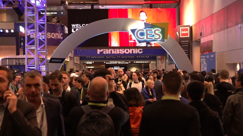 CES attendees pass under an archway in a crowded hallway of the Las Vegas Convention Center