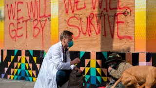 Stuart Malcolm, a doctor with the Haight Ashbury Free Clinic, speaks with homeless people about the coronavirus.