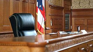 the judge's stand inside a courtroom with a US flag in the background