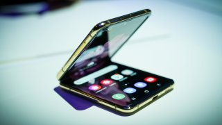 A folding smartphone with gold edges on a white tabletop