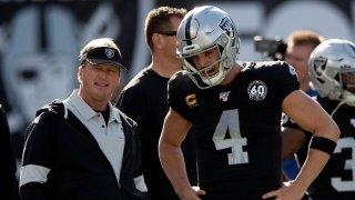 Jon Gruden of the Oakland Raiders talks to quarterback Derek Carr.