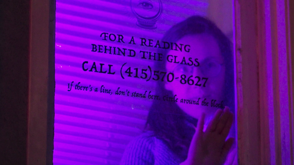 """A woman lit by dim purple light attaches a clear sign to the inside of a window. """"For a reading behind the glass,"""" it says, and offers a (415) phone number."""