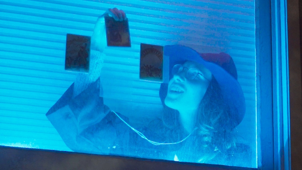 A woman inside a blue-lit window at night pulls one of three tarot cards from clear plastic holders affixed to the window glass.