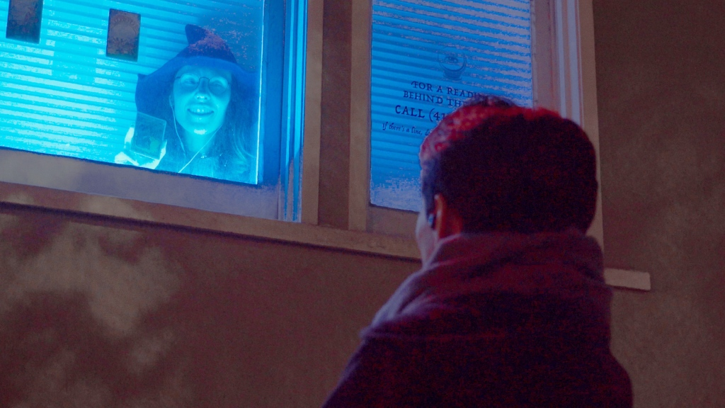 a woman in a blue-lit window shows a tarot card to a man standing out on the dark street. we see only the back of his head.