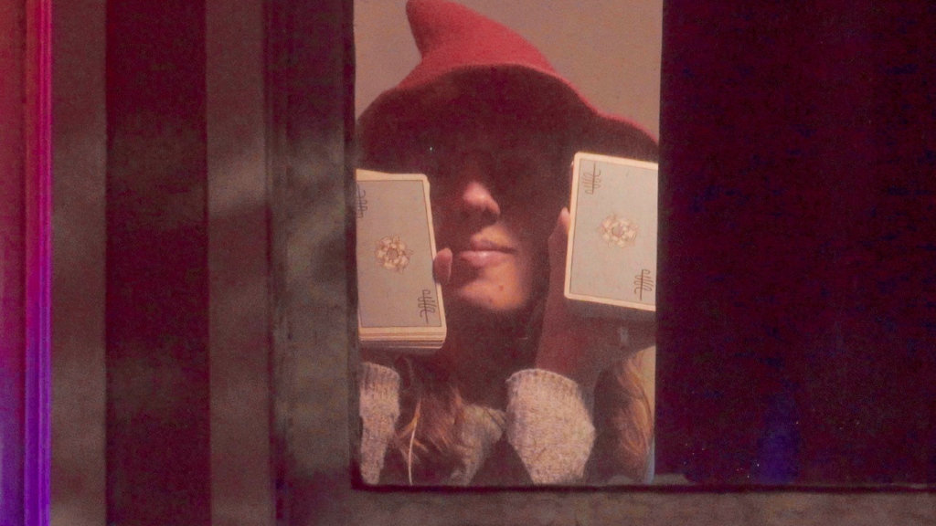 A woman wearing a hat holds up two piles of cards in her two hands from behind a window