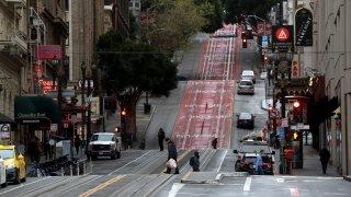 Few pedestrians walk along Powell Street in San Francisco during commute hours.