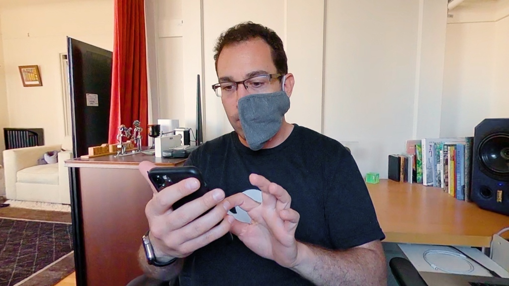 a man wearing a mask looks at an iphone and touches it with his index finger