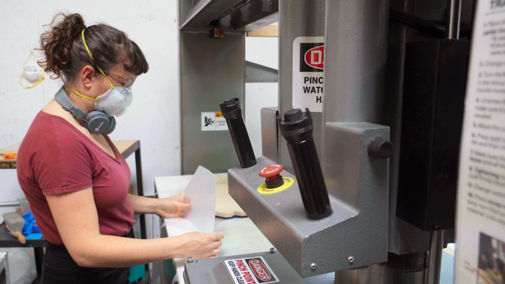 a woman stands at a large machine, holding two five-sided pieces of clear plastic in her hands