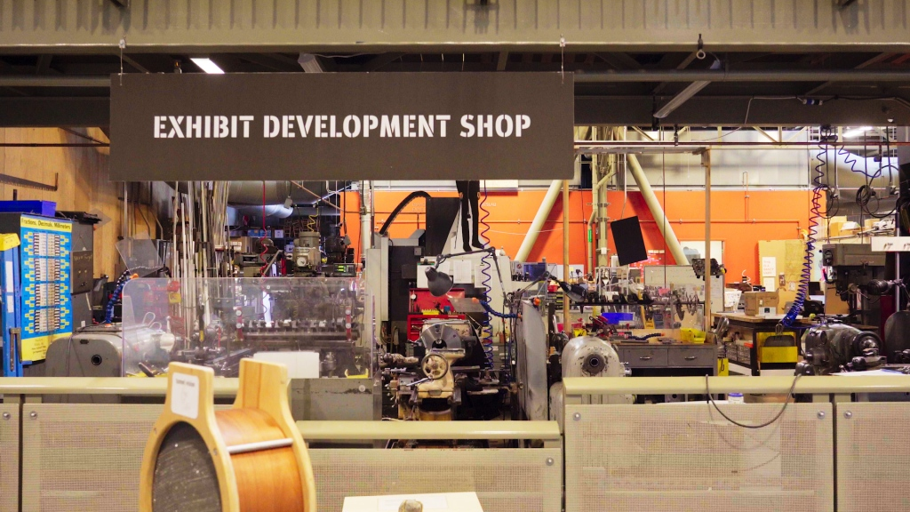 """""""exhibit development shop"""" sign above a messy workshop full of equipment"""