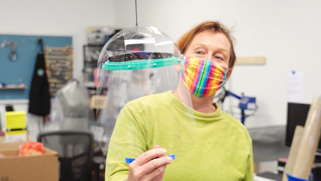 a woman with a colorful mask over her nose and mouth holds up a clear plastic face shield