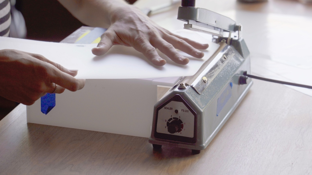 a woman's hands align a five-sided piece of clear plastic with the hot edge of a heat sealing machine