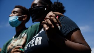 Isaiah Chatman, left, and his girlfriend, Angelah Hackney, both of Oakland, hold their hands while listening to a speaker before marching in Dublin.
