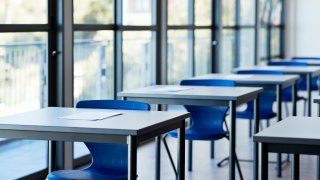 Papers on desks by windows in classroom