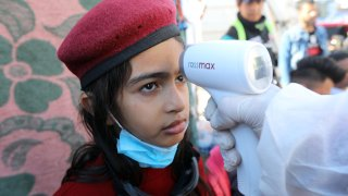 A girl receives a temperature test at Tahrir Square in Baghdad, Iraq
