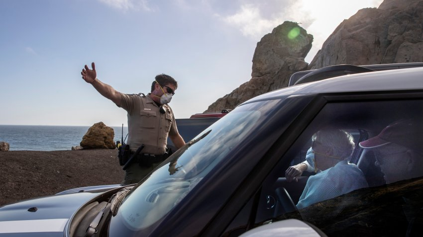 California State Parks ranger David Gunn, left, warns visitors to Pt. Mugu that parking is not allowed due to coronavirus and social distancing restrictions on Saturday, April 11, 2020 in Point Mugu, CA.