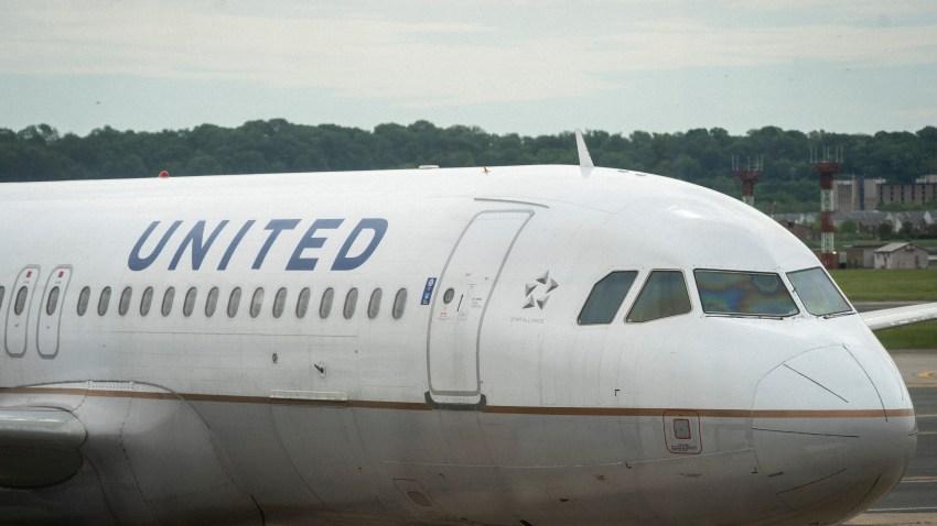 A United Airlines plane sits at a gate Ronald Reagan Washington National Airport, May 5, 2020 in Arlington, Virginia.