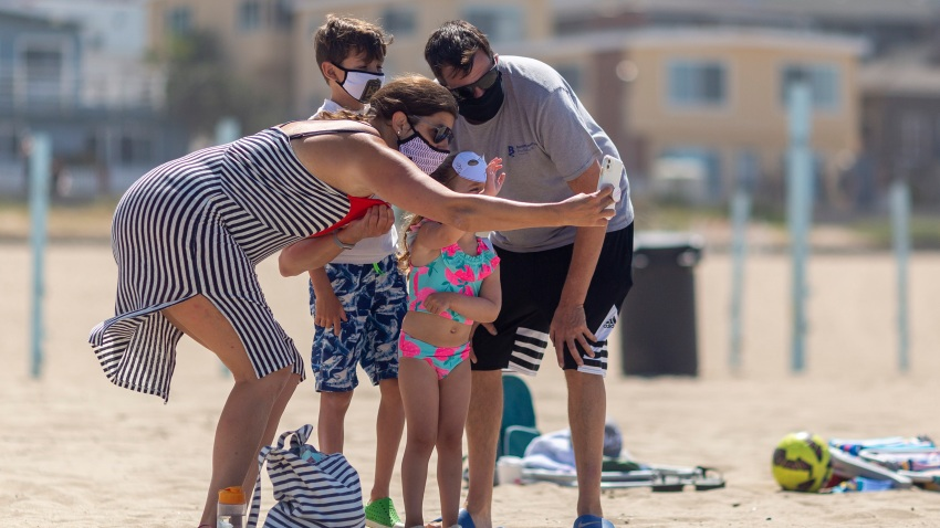 A family takes a group selfie in masks as people visit one of Los Angeles County's recently reopened beaches during the coronavirus pandemic, in Manhattan Beach, California on May 17, 2020.