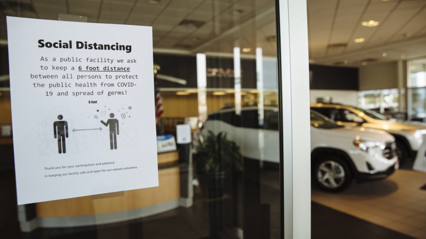 A sign advising customers to practice social distancing is displayed on the door of a General Motors Co. Buick and GMC car dealership