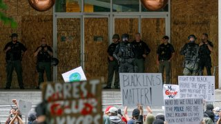 Heavily-armed riot police stand on the porch of the damaged Portland Justice Center during the protests over the death of George Floyd